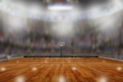 Basketball Arena With Copy Space. Low angle view of fictitious empty basketball arena with sports fans in the stands. Focus on foreground with deliberate shallow Royalty Free Stock Photo