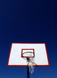 Basketball backboard. A view looking up at a white basketball backboard with red markings and a broken net, isolated against a graduated, deep blue sky or Stock Image