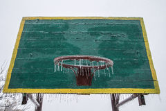 Basketball backboard and ring in winter. With a basketball hoop hanging icicles. Ice. Frost. No sports. No games. Stock Photo