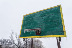Basketball backboard and ring in winter. With a basketball hoop hanging icicles. Ice. Frost. No sports. No games. Stock Image