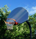 Basketball Backboard Streaked With Sunlight. In a park in spring on an old blacktop court Stock Image