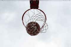 Basketball ball falling trough rim with net. Cloudy sky, outdoor court. Basketball hoop, basket against cloudy sky. Outdoor basketball court. Orange leather Royalty Free Stock Photo