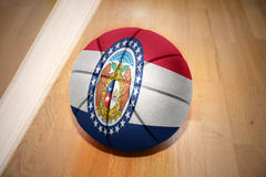 Basketball ball with the flag of missouri state. Lying on the floor near the white line Stock Photos