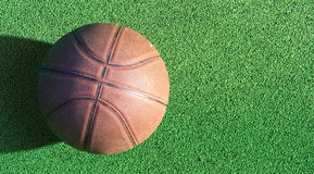 Basketball ball on green field floor Royalty Free Stock Images