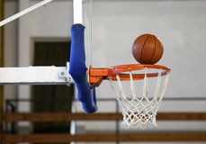 Basketball ball in hoop. Winning shot at basketball game - ball enters the hoop stock photography