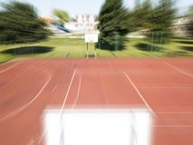 A basketball ball lies in front of a basketball ring at the stadium.Basketball court in the open air with artificial surface. Blur Stock Photography