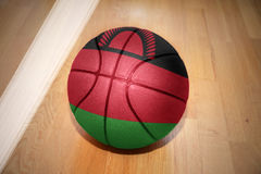 Basketball ball with the national flag of malawi. Lying on the floor near the white line Stock Photos