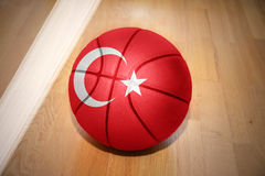 Basketball ball with the national flag of turkey. Lying on the floor near the white line stock photo