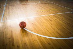 Basketball ball. Over floor in the gym stock image