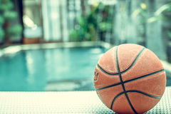 Basketball ball on a swimming pool background, tropical sport scene. Basketball ball on a swimming pool background, sport scene stock image