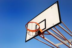 Basketball basket. The image shows a white basketball basket on an outdoor sports ground. You see the board and the orange hoop with a deep blue sky as royalty free stock photo