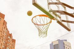 Basketball basket on the background of city houses. Street basketball. Basketball basket on the background of city houses and flying into her ball. Street royalty free stock photos