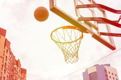 Basketball basket on the background of city houses. Street basketball. Basketball basket on the background of city houses and flying into her ball. Photo in warm stock photos