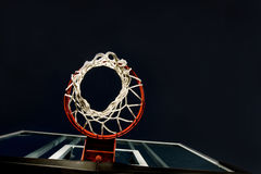 Basketball Basket Below. Basketball basket and net shot from below. A unique view in a basketball arena with only the basket lit. Lots of Copy space room Stock Photos