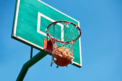 Basketball basket on street sport ground and ball on blue. Basketball basket on a street sport ground and an orange ball on a blue sky background royalty free stock image