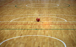 Basketball in the basketball court with a wooden parquet and gam. Basketball court with a wooden parquet and the ball Royalty Free Stock Images