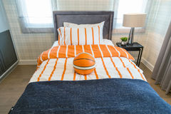 A basketball on the bed with bedside lamp in bedroom kids. Royalty Free Stock Images