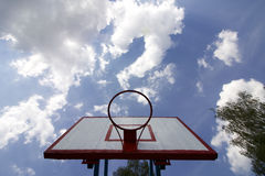 Basketball board without net. Old, wooden planks. Painted. Located on a background of blue sky with clouds. Sport games in the yar Royalty Free Stock Image