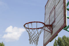 Basketball board with a net. Old, wooden planks. Painted. Located on a background of blue sky with clouds. Sport games in the yard Royalty Free Stock Photo