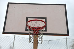 Basketball board under cloudy sky in a school yard. Concept of k Royalty Free Stock Images