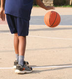 Basketball Boy. Shot of the lower half of a young boy dribbling a basketball Stock Photography