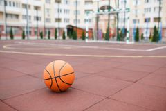Basketball, a bright, new ball lies on the red, rubber coating of the stadium. Basketball, bright, new ball lies on the red, rubber coating of the open stadium Stock Image