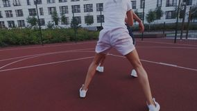 Basketball challenge or sport competition on outdoor. Young man and girl plays on open stadium. Girl protect basket hoop stock video footage