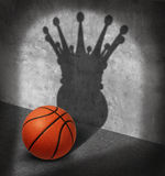 Basketball Champion. And championship concept as a ball casting a shadow wearing a king crown as a metaphor for visualizing victory on the court shooting hoops Royalty Free Stock Photography
