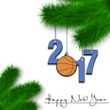 Basketball and 2017 on a Christmas tree branch. Happy New Year and numbers 2017 and basketball ball as a Christmas decorations hanging on a Christmas tree branch Royalty Free Stock Photo