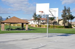 Basketball court. An empty basketball court at a local park in the spring with ablue sky and clouds Royalty Free Stock Image