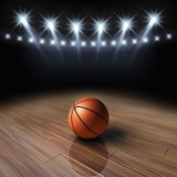 Basketball court. Ball on wooden basketball court with spotlights Royalty Free Stock Photos
