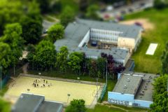 Basketball court buildings trees and players with Stock Images
