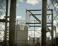 Basketball court in chain link. A basketball hoop seen through a chain link fence stock photography