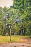 Basketball court in a city park. Basketball basket among the green trees stock images