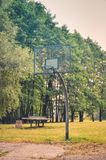 Basketball court in a city park. Basketball basket among the green trees royalty free stock photography