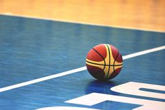Basketball on court. Closeup of basketball on blue wooden court royalty free stock image