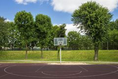 Basketball court in the outdoor schoolyard on a bright summer day. Royalty Free Stock Photo