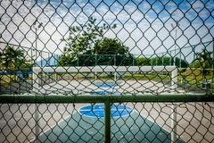 Basketball court and soccer field in public park behind fence - Royalty Free Stock Image