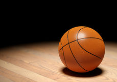 Basketball on dark background. Basketball ball on parquet floor, black background. 3D illustration Stock Photography