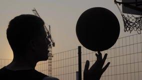 Basketball, der auf einen Mannfinger balanciert und spinnt stock footage
