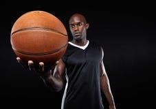 Basketball in der Hand des afrikanischen Sportlers Lizenzfreies Stockbild