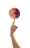 Basketball Earth. A person balances a basketball with Earth-like qualities on her finger. This symbolizes how many sports like basketball can bring people from Royalty Free Stock Image