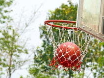 Basketball falls through basketball hoop and net Royalty Free Stock Image