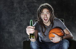 Basketball fan watching television. Happy young man watching sport on television stock photos