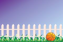 Basketball and fence. Basketball on grass and fence Royalty Free Stock Photography