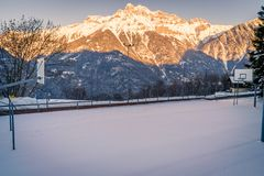 Basketball field covered with snow. And mountains in the background Stock Image