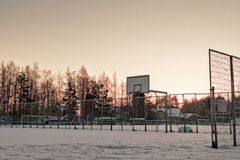 Basketball Field Covered with Snow. The town basketball field is covered with heavy snow at the rural town of Oulainen, Finland. The sun is setting early in this Royalty Free Stock Photo