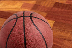 Basketball on floor of hard wood court. Close up of basketball on floor of hard wood court Royalty Free Stock Images