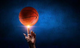 Basketball game concept. Male hand spinning basketball bal on finger Royalty Free Stock Photos