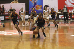 Basketball game between high school. Women's basketball player in action during a league match between middle school students in Solo, Central Java, Indonesia Royalty Free Stock Photography